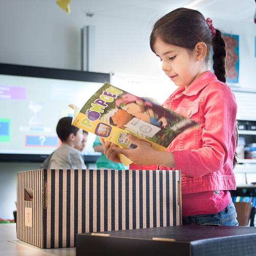 Kind leest tijdschrift in de klas